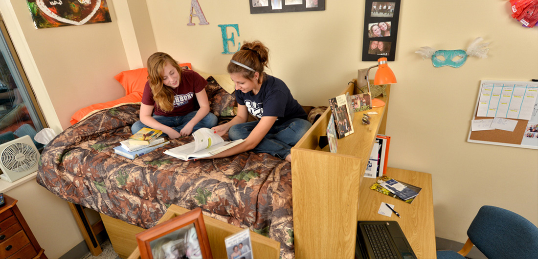 Two female Washburn students study on a bed in the Living Learning Center.