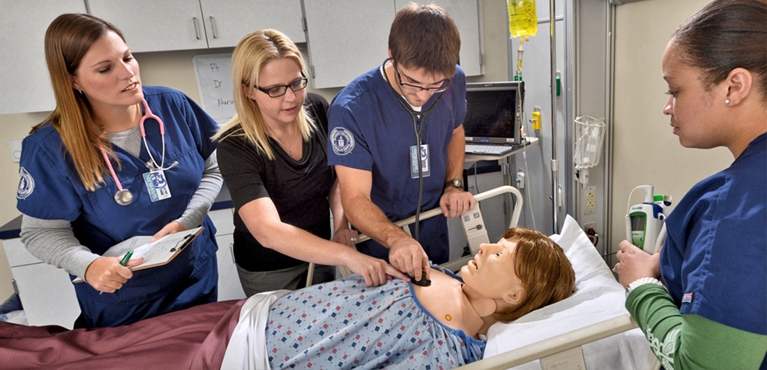 Three students and a female nursing faculty member circle a simulation patient dummy in a simulation hospital room.