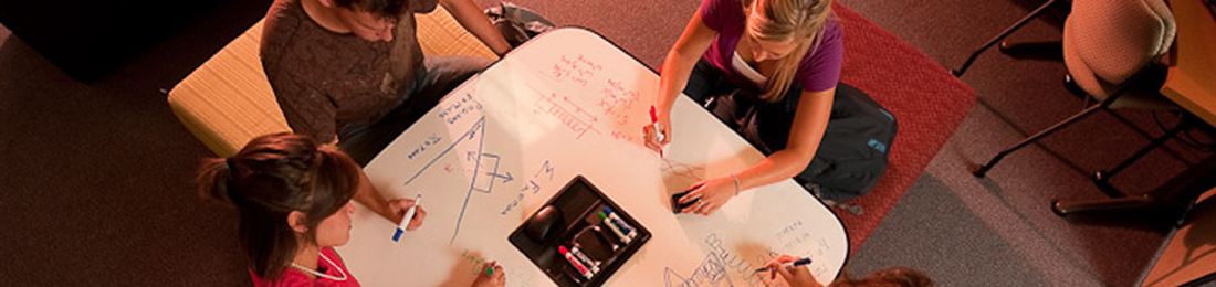 Students at a white board table in Mabee Library