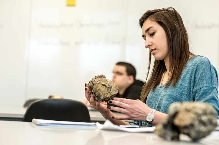 student inspects fossil in classroom