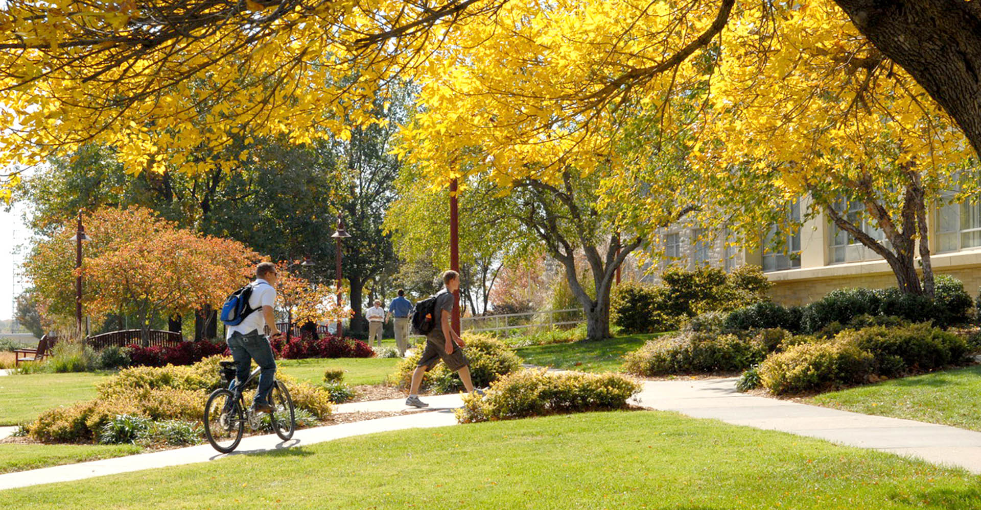 campus in fall with students walking and riding bikes