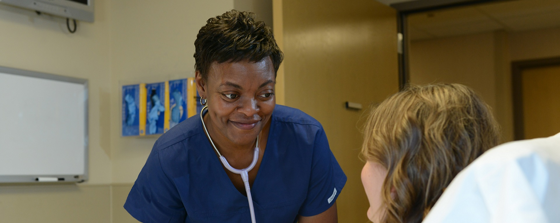 A smiling black nurse bending over to help a patient in bed.