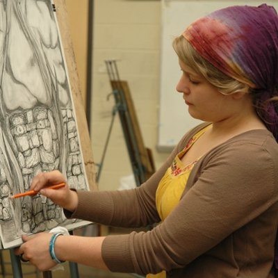 A Washburn art student works on a painting during class in the Art Building.