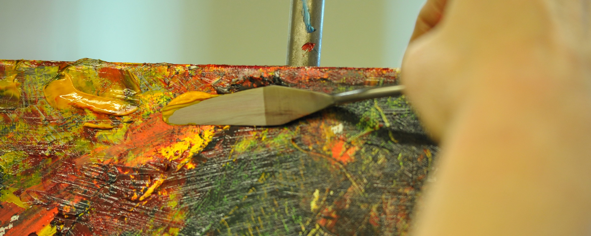 Close up of a student's hand painting on an easel