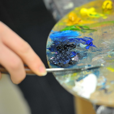 Close up of a student's hand painting and holding a paint palette