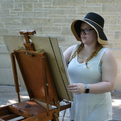 Student drawing on easel outside on campus