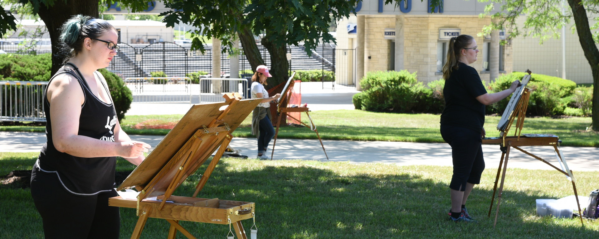 Three students drawing on easels on Union Lawn