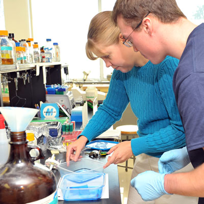 Biology instructor and student working with chemicals