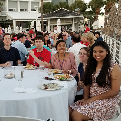 Students sitting at a conference dinner table, outside