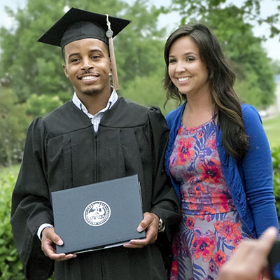 Male student in graduation robe with diploma cover, standing next to woman, having picture taken