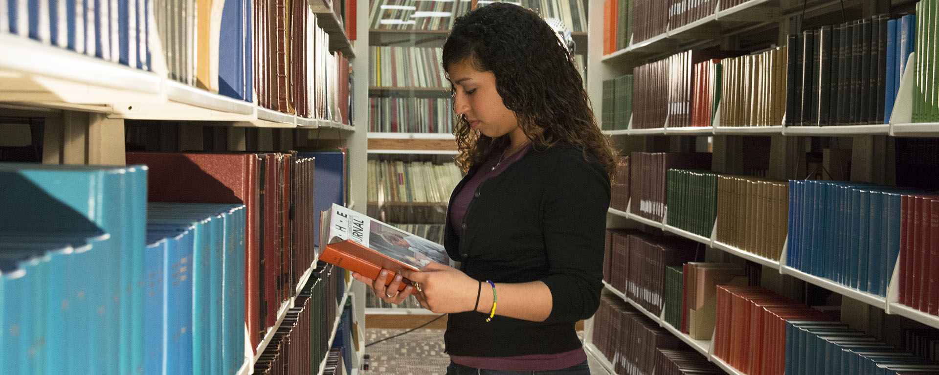 Student looking at book in Mabee Library stacks