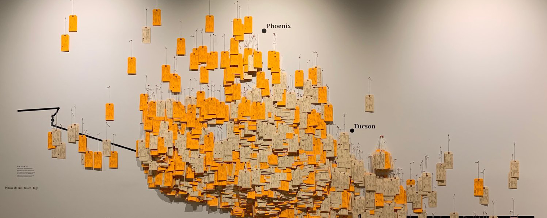 This image of the exhibit shows some of the nearly 4,000 handwritten toe tags representing migrants who have died trying to cross the southern U.S. border between 1994 and 2019. These tags are geolocated on a wall map of the desert showing the exact locations where remains were found.