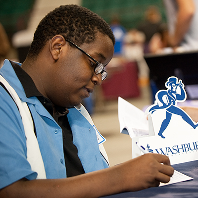A Washburn student fills out paperwork during a recruiting event.
