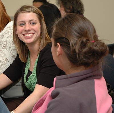 A Washburn student smiles while chatting with a classmate during a School of Nursing class.