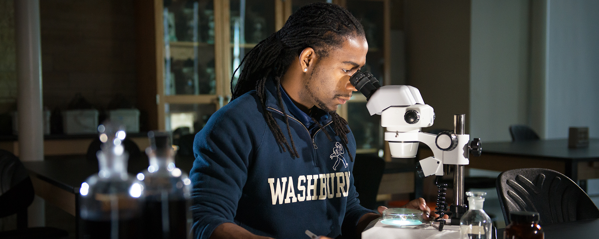 A Washburn student uses a microscope in a classroom at Stoffer Science Hall.