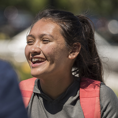 A Washburn student laughs while talking to a classmate in front of the Welcome Center.