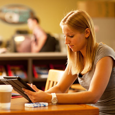 A student scans her tablet in Mabee Library on Washburn's campus.
