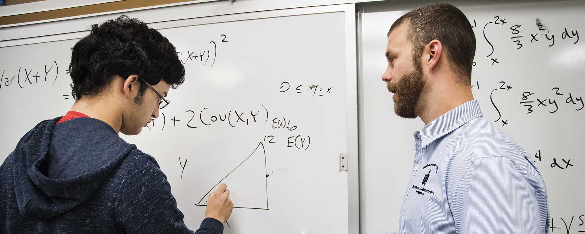 A math professor works with a Washburn student on a formula during class.
