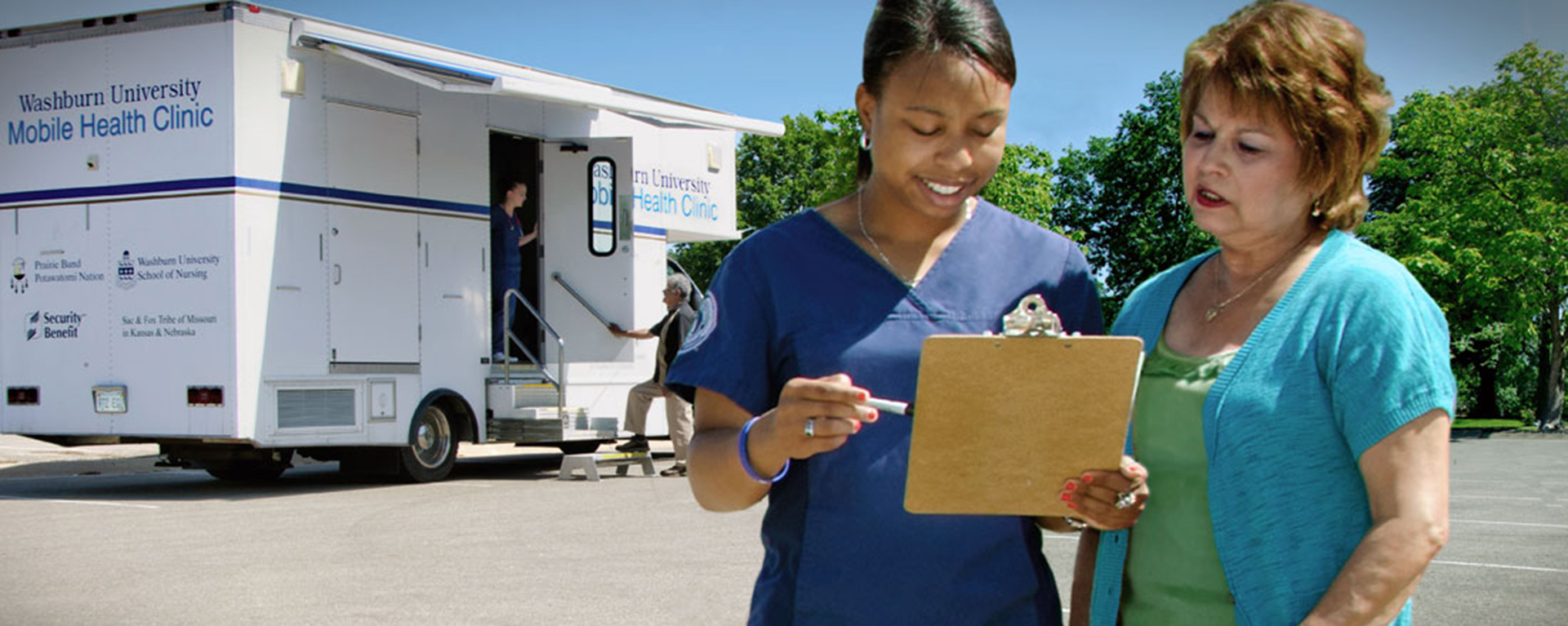 a nurse speaking with a woman in front of a mobile nursing vehicle