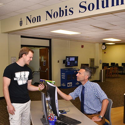 staff member helps smiling student at info desk