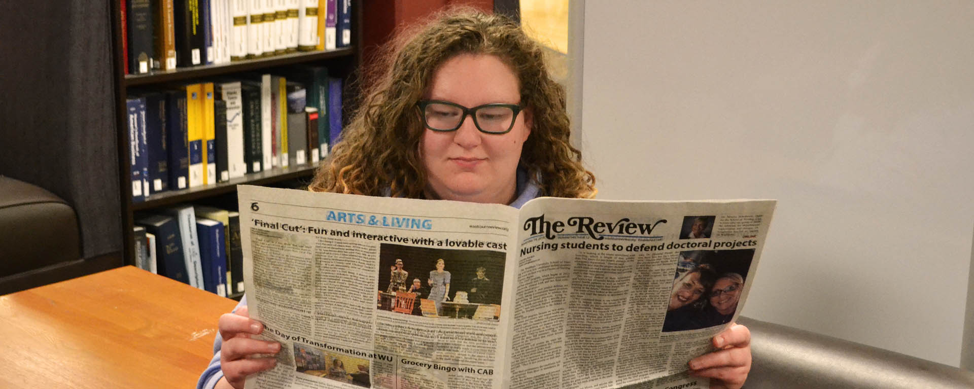 Student in library reading newspaper