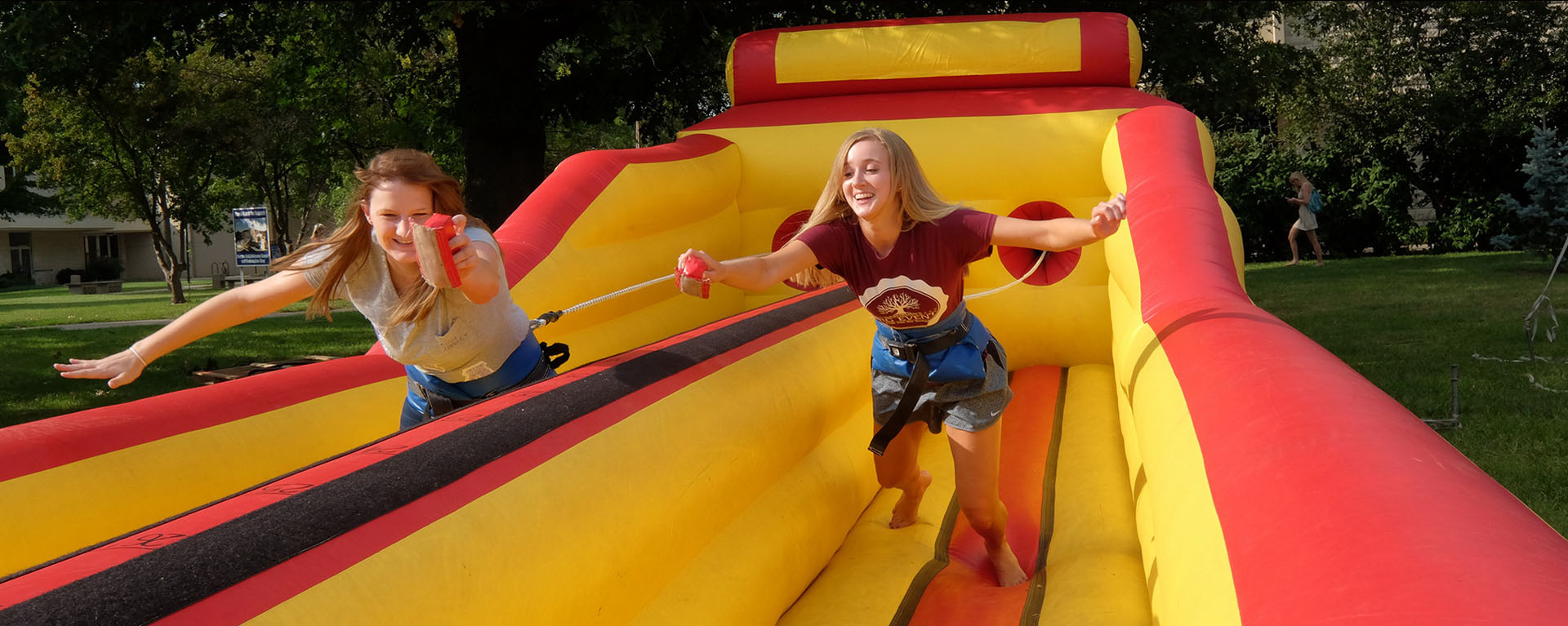 two female students smiling, jumping down a slide