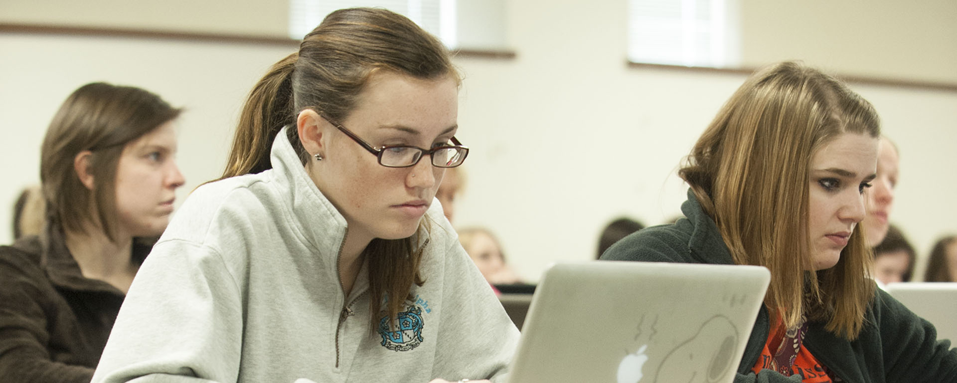A Washburn student types on her laptop to take notes during class