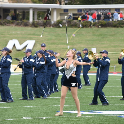 Band and baton twirler performing on football field