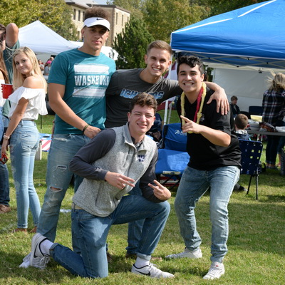 Four students smiling at the camera while tailgating
