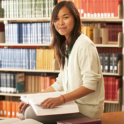 Asian female student in Mabee Library, sitting on table in front of bookshelves, looking at camera.